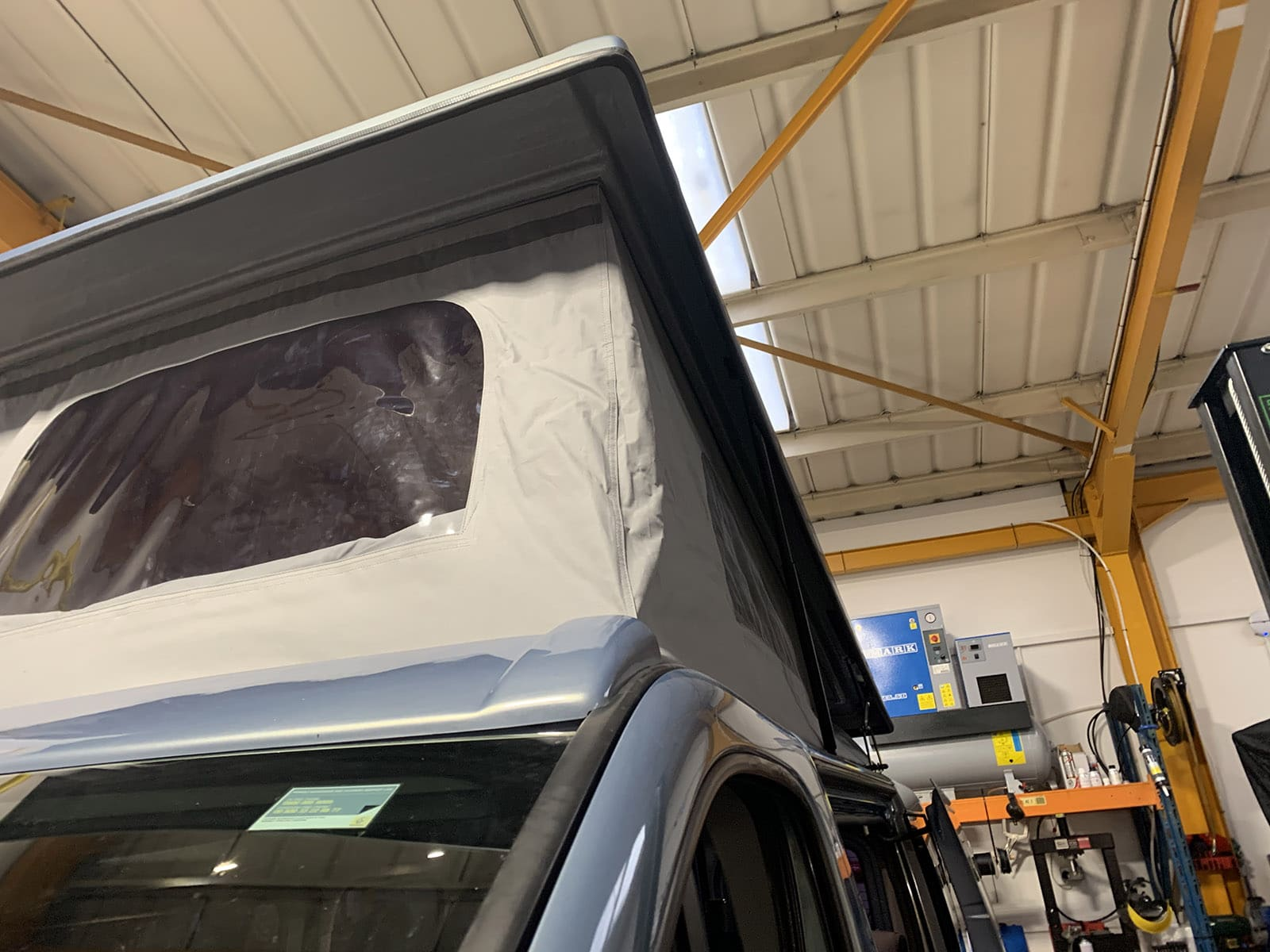 A pop top conversion with window being installed at our workshop